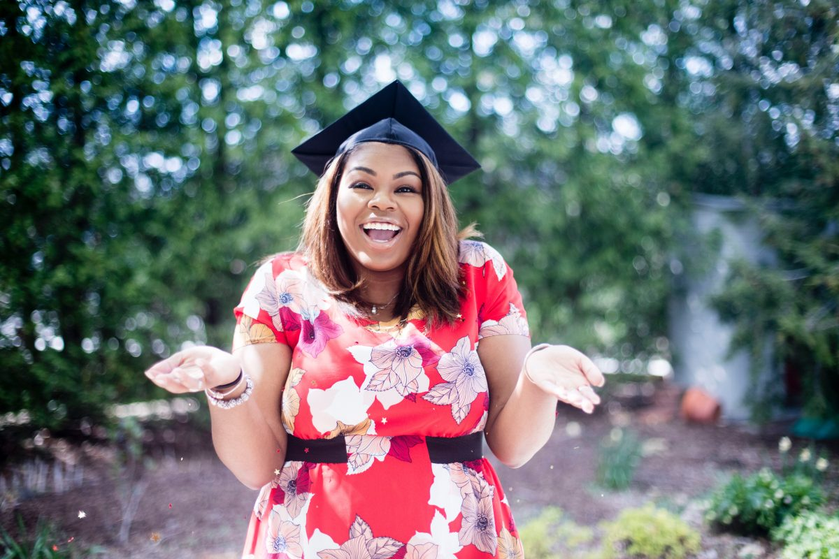 Young woman, recent college graduate, standing in a forest with her hands palms up.